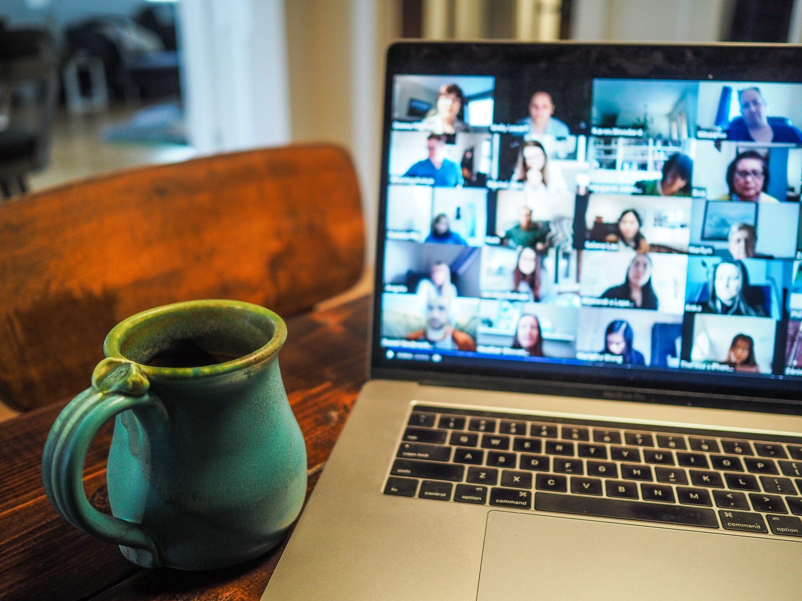 Verkkokokoukseen osallistujien kuvia kannettavan tietokoneen ruudulla ja kahvikuppi