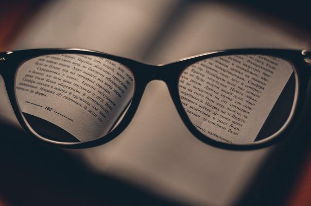 Etualalla silmälasit, joiden läpi kirjan teksti näkyy kirkkaasti. Silmälasien ulkopuolella teksti sumeaa.